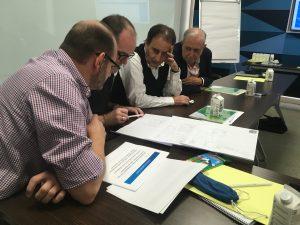 Un grupo de asistentes estudian unos planos