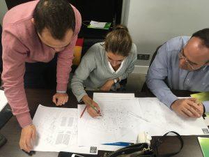 Un grupo de asistentes trabajan sobre plano