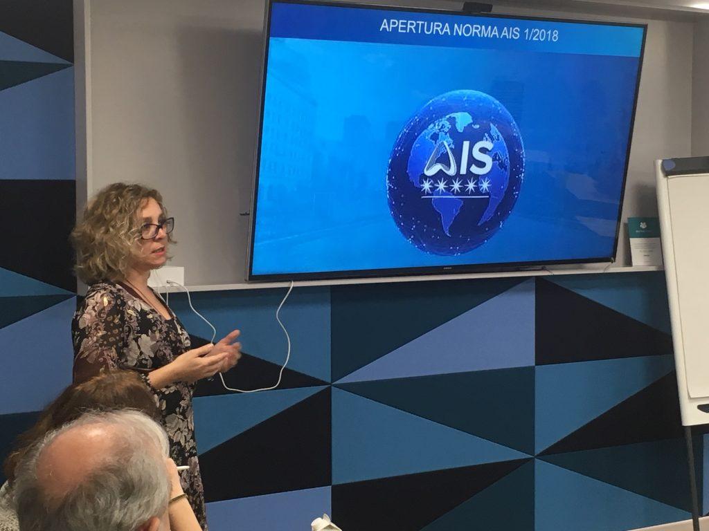 Rosa Rodríguez habla junto al logo de AIS