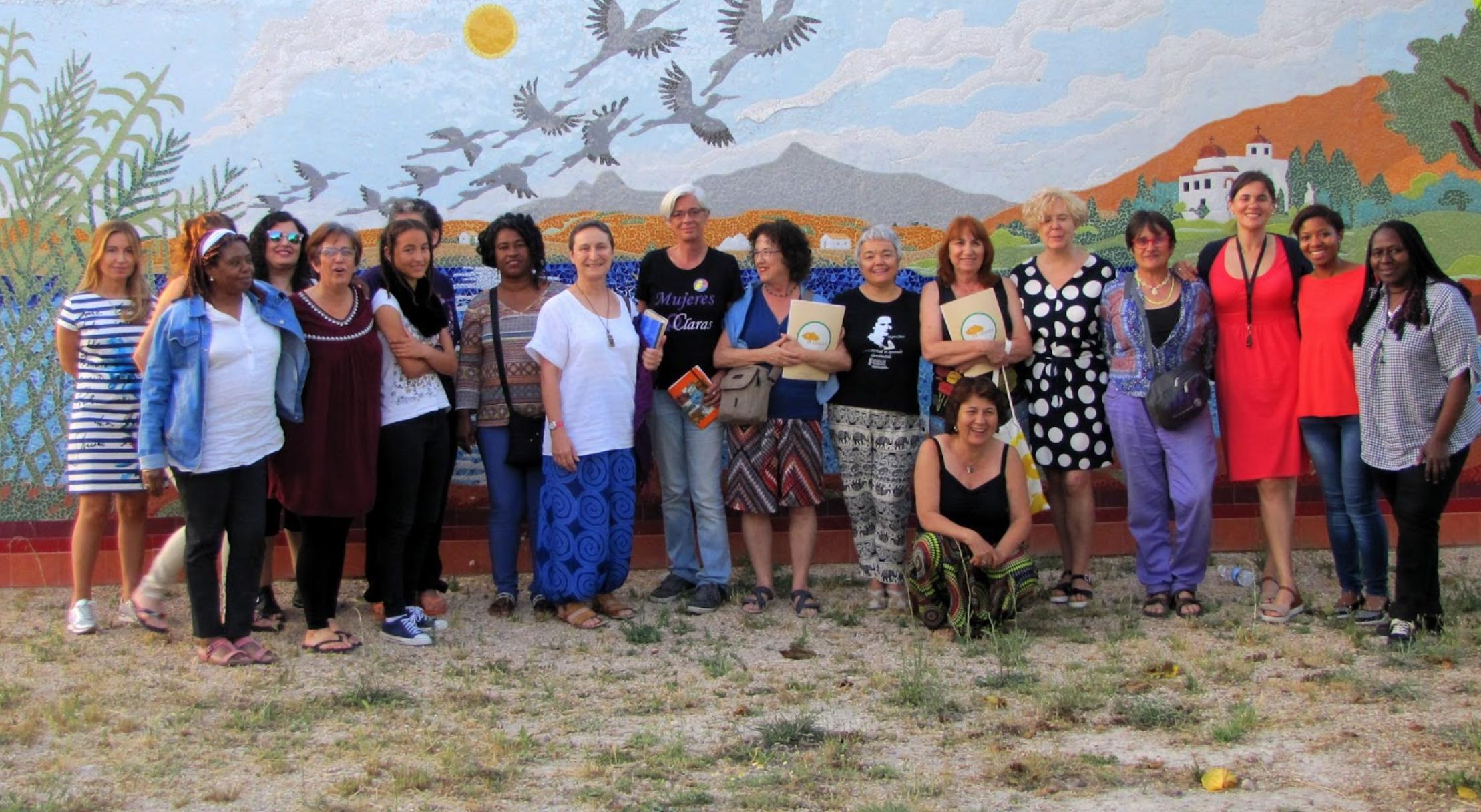 Aparece un grupo de personas delante de un mural con un paisaje