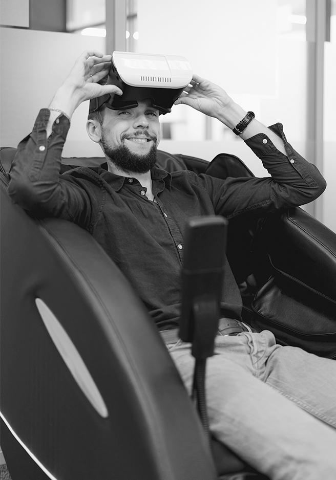 Aparece un joven sentado en un sofá con unas gafas de realidad virtual